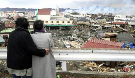 Two-women-look-at-buildings-that-were-devastated-by-massive-quake-and-tsunami-at-Japan
